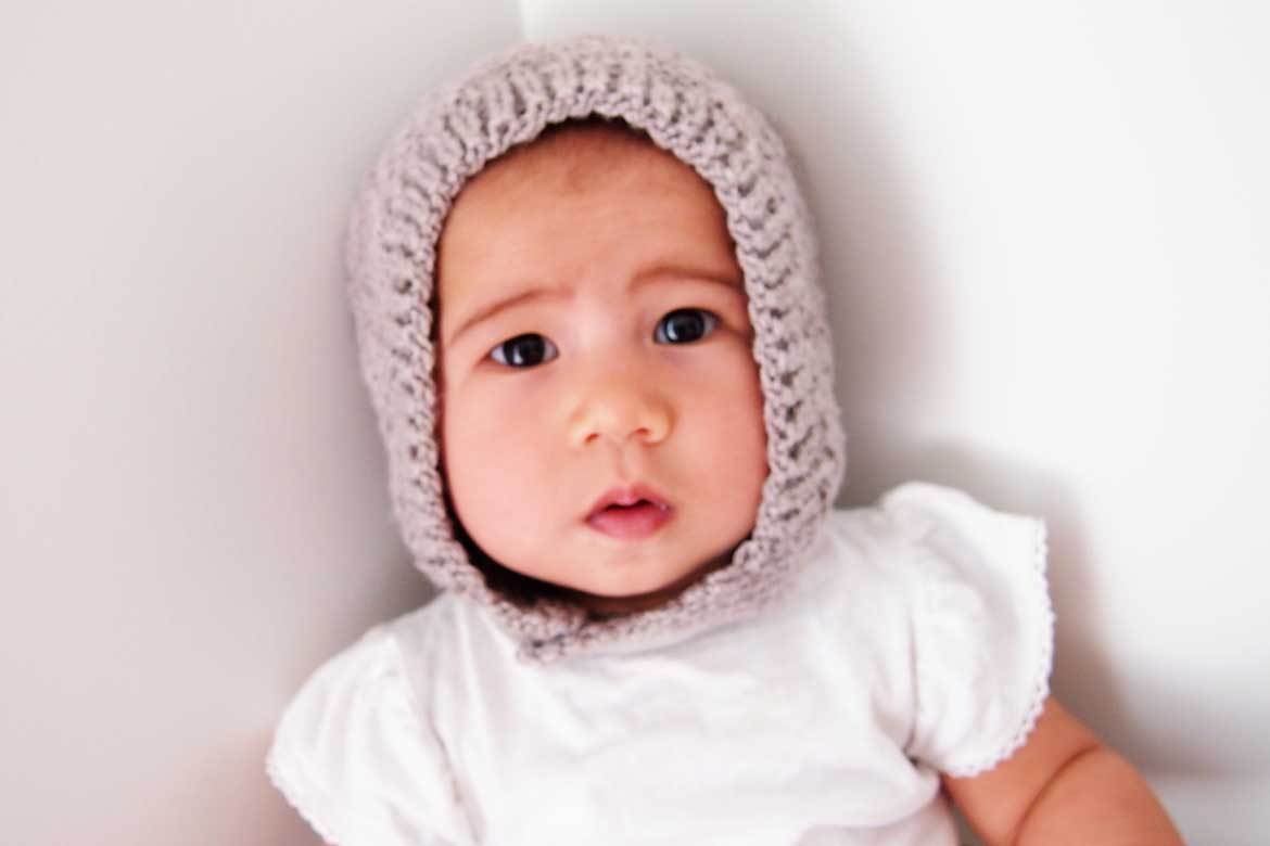 Free Baby Knitting Pattern | This cute bonnet hat is a free sewing pattern and makes a great beginner knitting project.