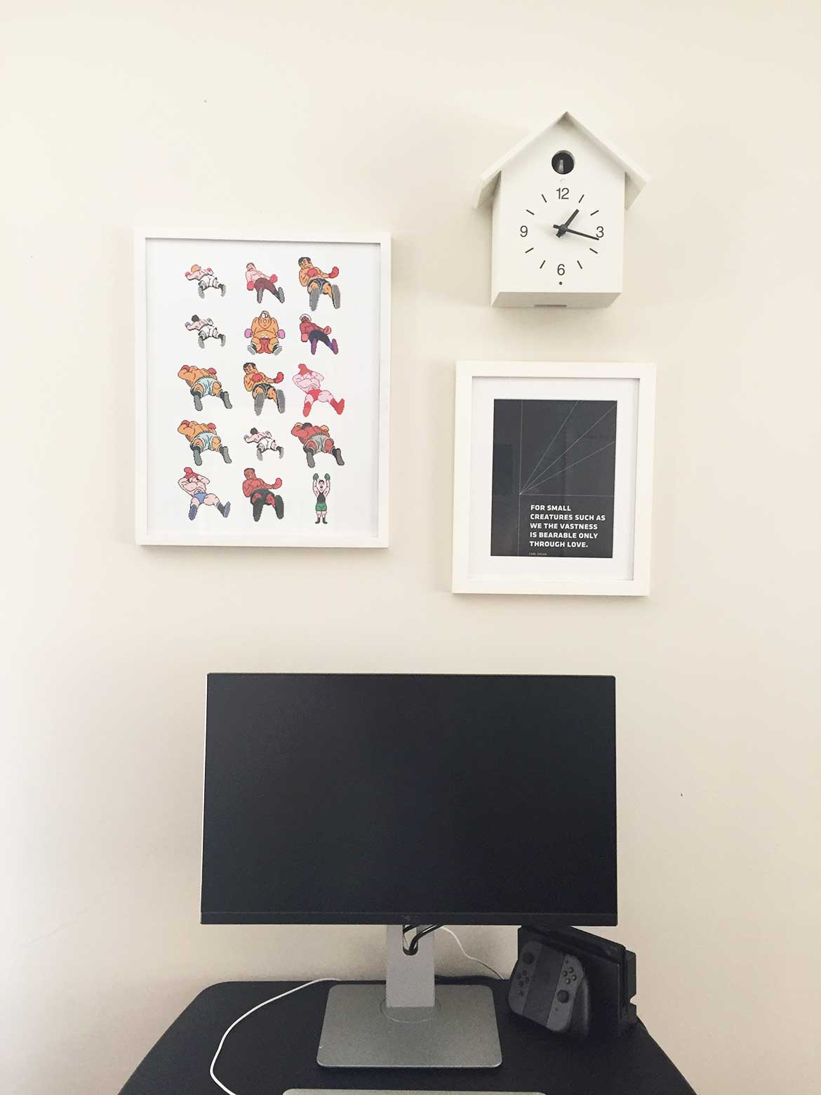 The space above the standing desk is decorated with prints and a Muji cuckoo clock.